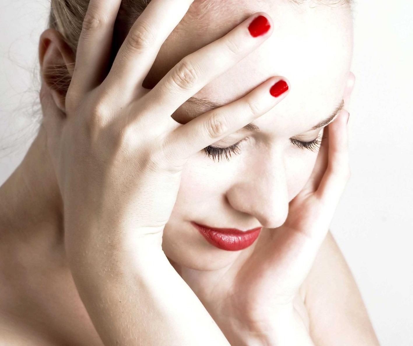Женщина держится за лоб при головной боли