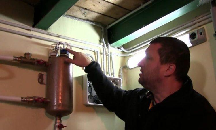 Мужчина показывает рукой на электротел в частном доме